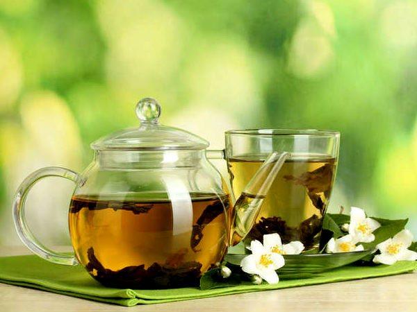 Зеленый чай на столе в чашке и чайнике