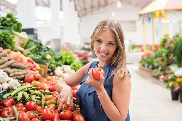 Женщина держит помидор