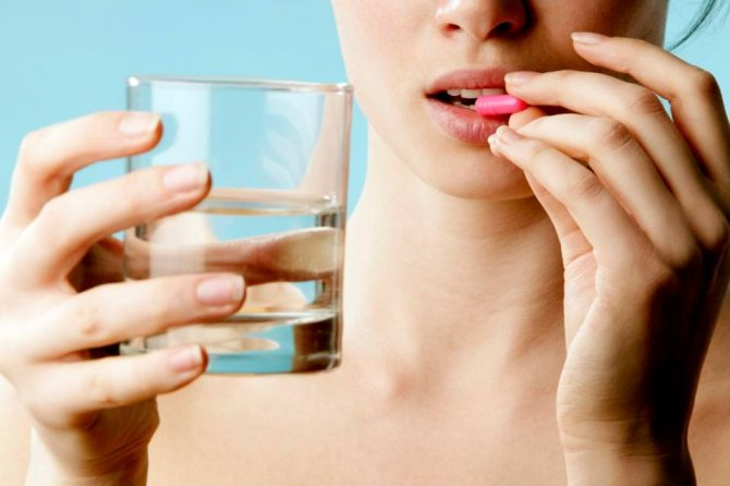 Женщина пьет витамины